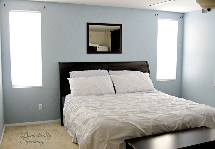 Updated a master bedroom with a shimmery silver blue stencil focal wall