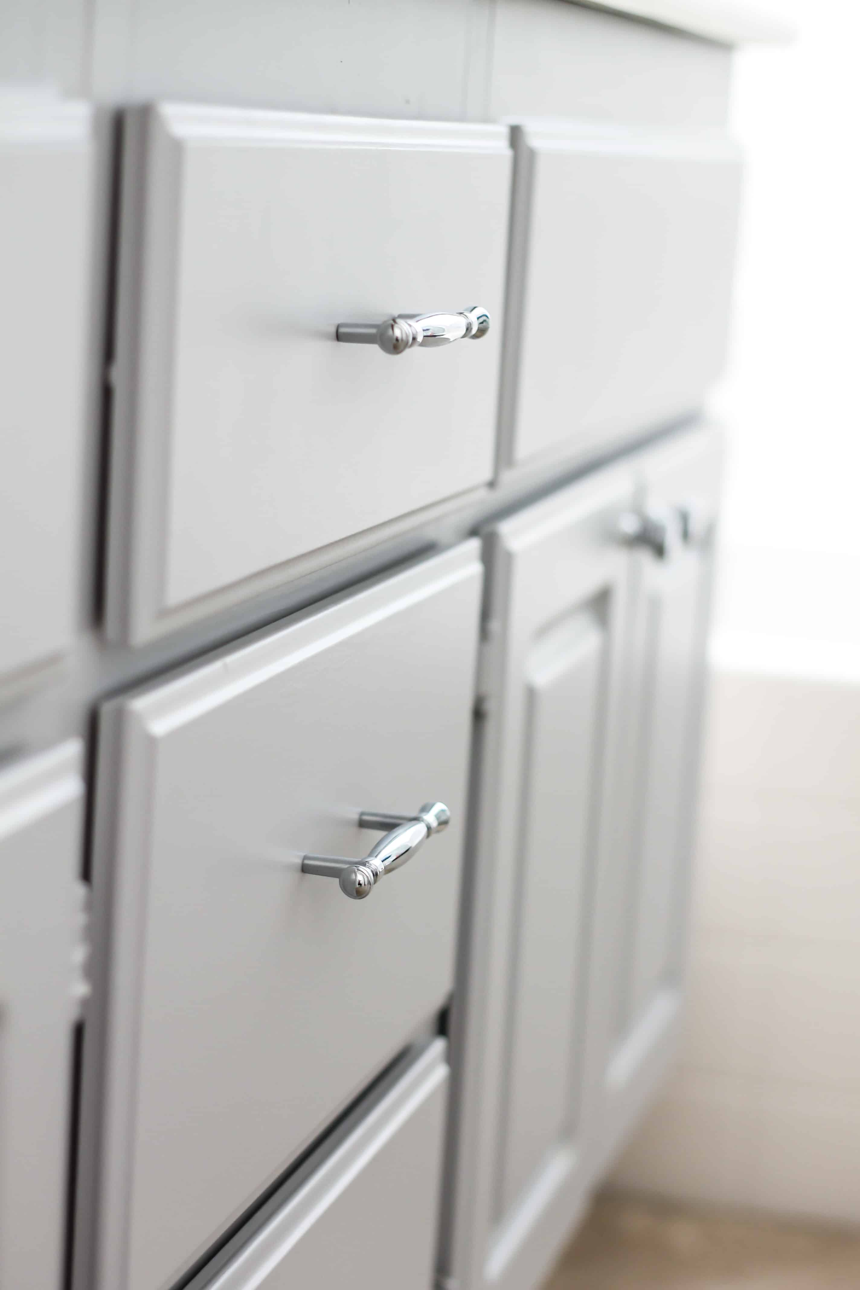 Upgrade your Boring Builder Grade bathroom cabinets with paint & hardware - get all the details here!
