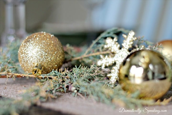 greenery and gold bulbs with a burlap runner Christmas tablescape