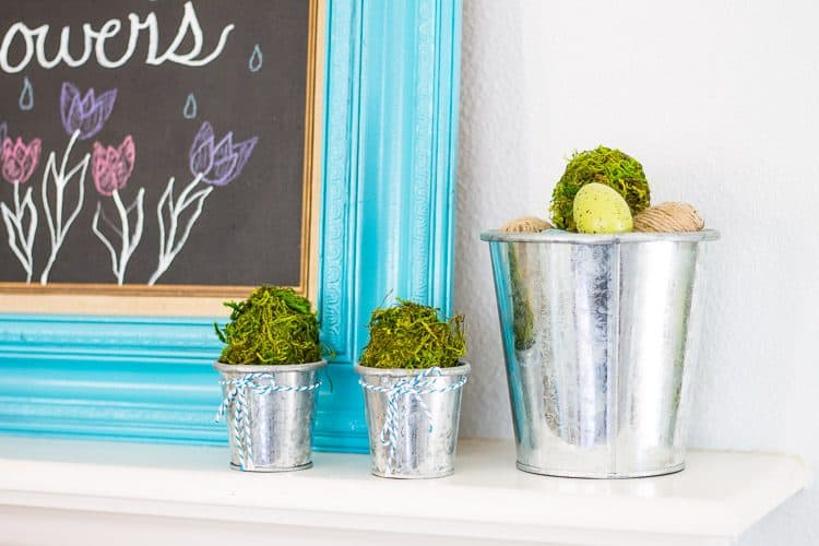 Chalkboard Spring Mantel with blue and green mason jars and white daisies.  A simple Spring Mantel full of color with touches of green moss and galvanized buckets.