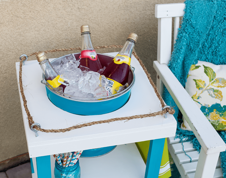 A cute striped bucket is perfect for keeping drinks cold in this Beverage Stand