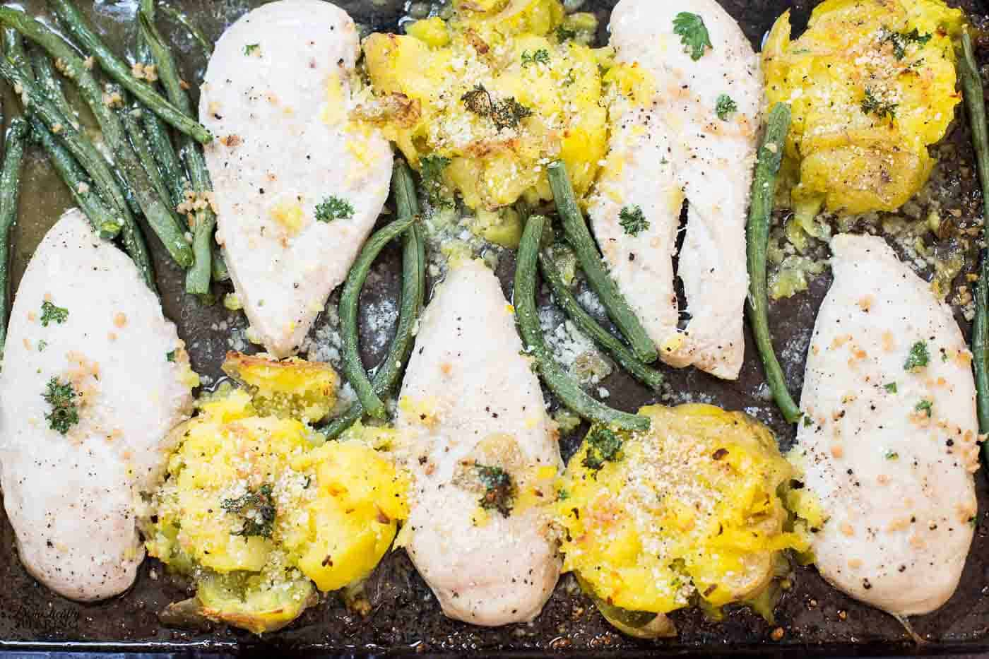 One Pan Chicken with Smashed Potatoes with roasted green beans all topped with a creamy butter, parmesan garlic sauce.