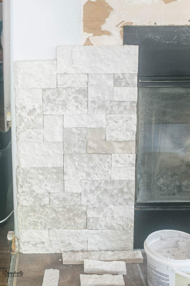 Putting the faux stone around the fireplace.