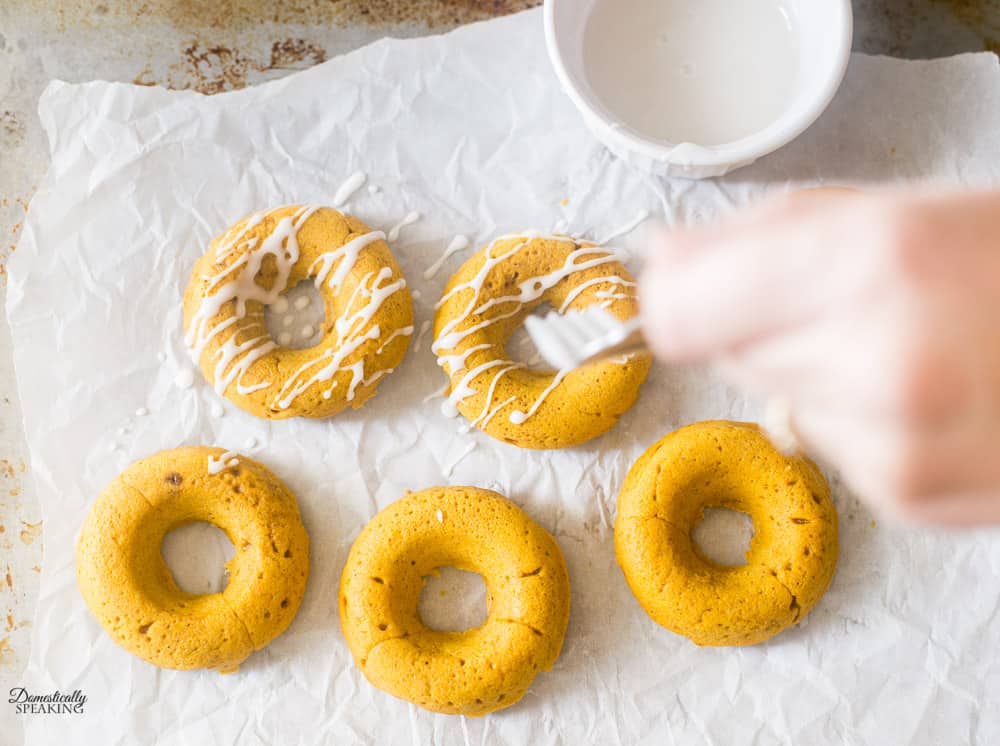 Drizzling glaze on the pumpkin spice donuts.