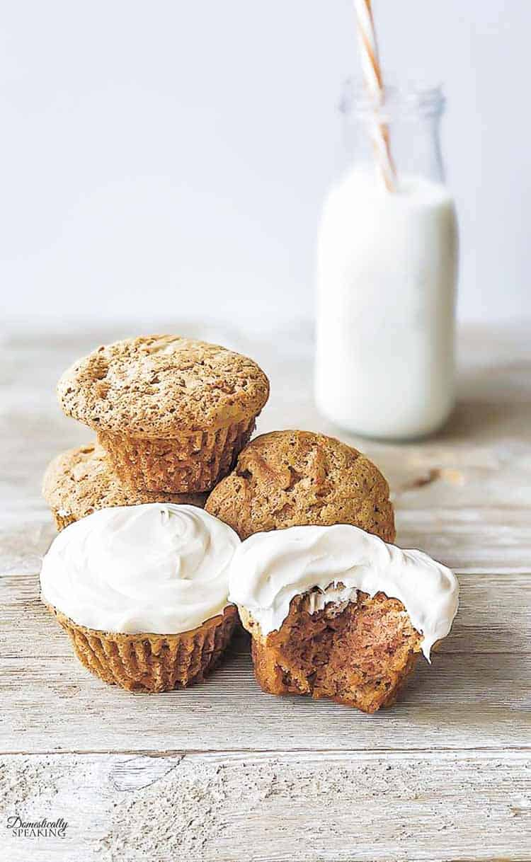 Simple Carrot Cake Cupcakes on a wood board with a jug of milk