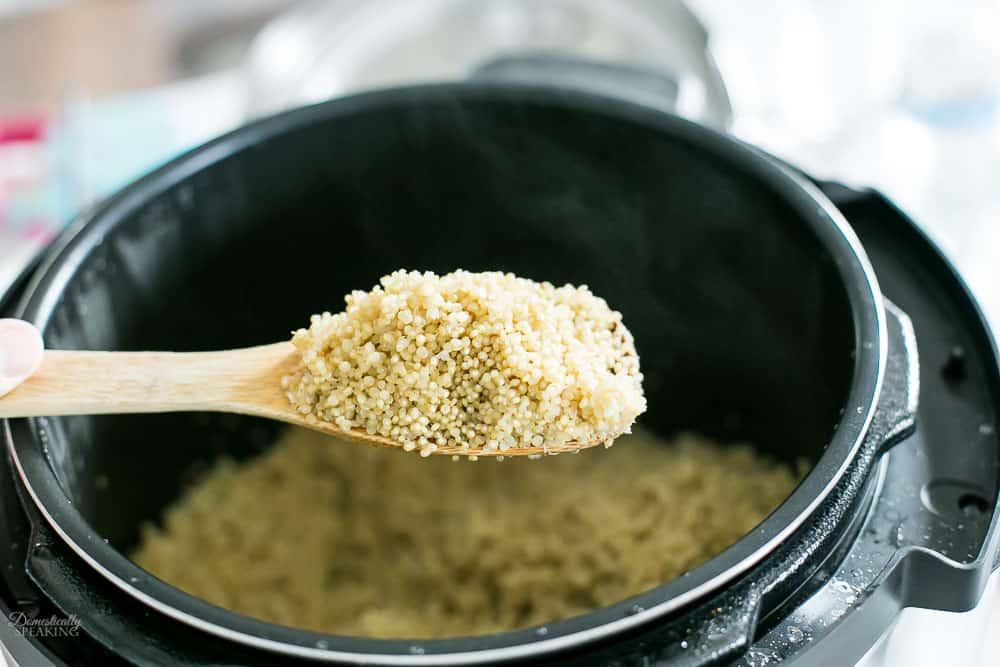 Quinoa on a wooden spoon over a pot