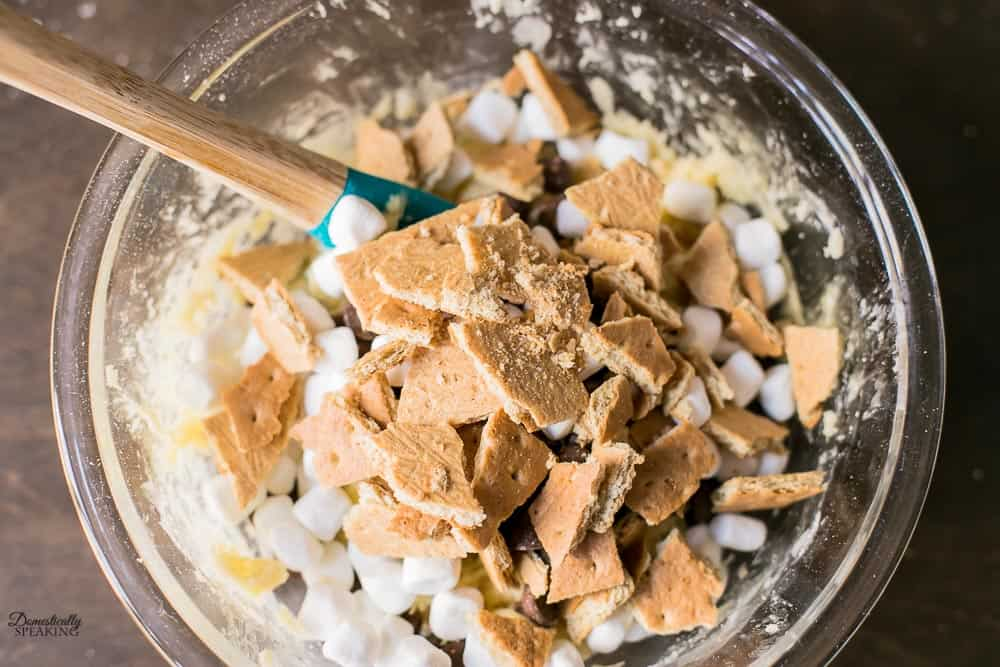 Adding the chocolate chips, mini marshmallows, and chunks of graham crackers to the cake mix bar cookies batter.