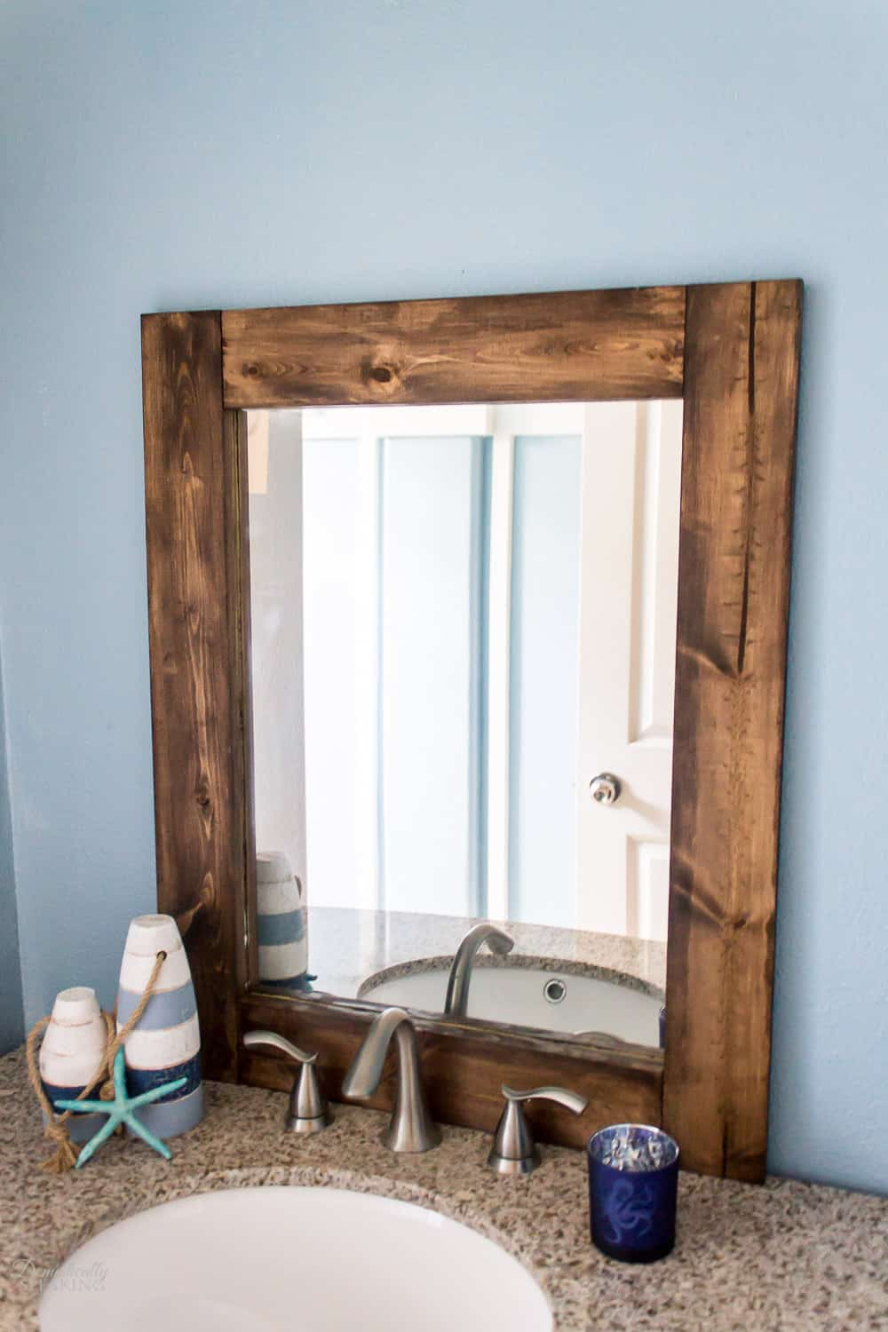 DIY Rustic Bathroom Mirror from an ornate thrift store mirror. Learn how to remove the glass and create a chunky wood framed mirror.