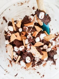 Adding the mini marshmallows and chunks of graham crackers to the Smores Cake Brownies.