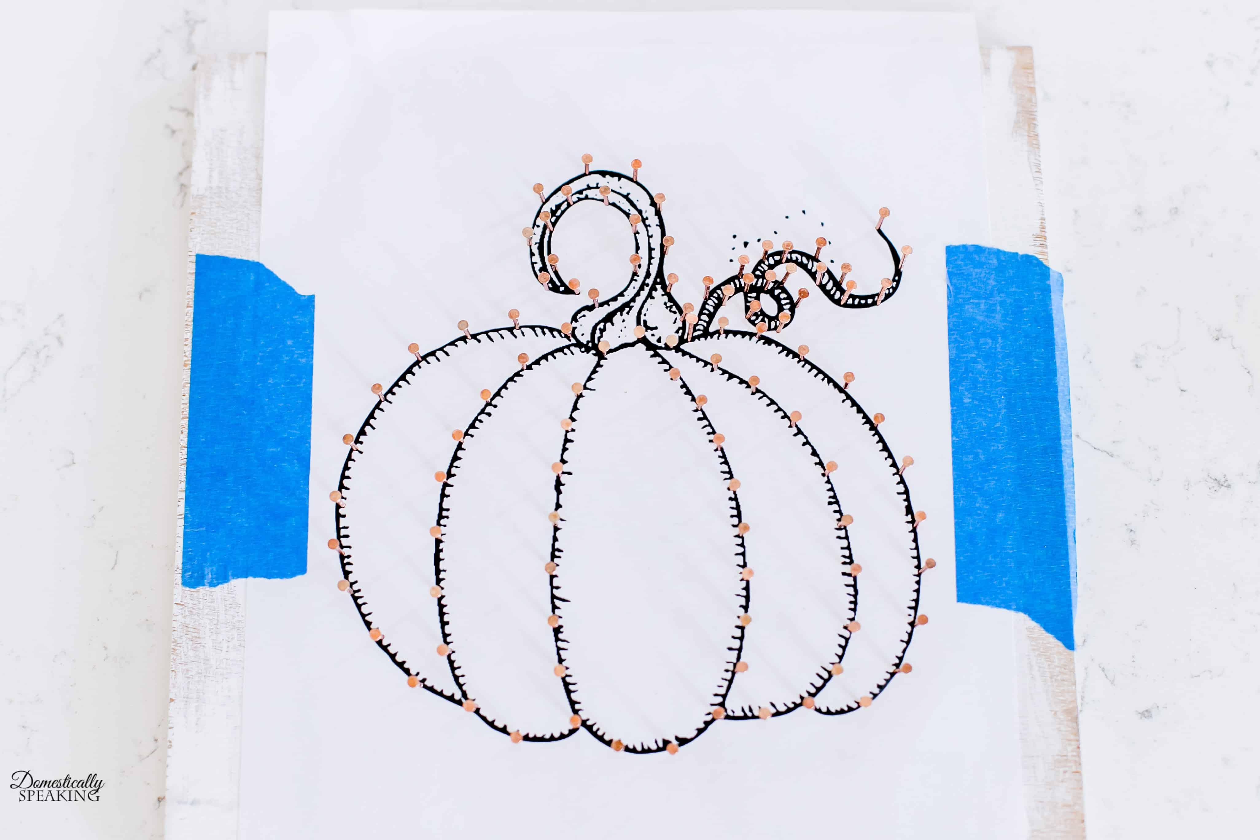 Adding the copper nails to create the copper pumpkin.
