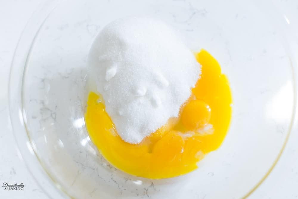 Adding sugar to egg yolks for custard.