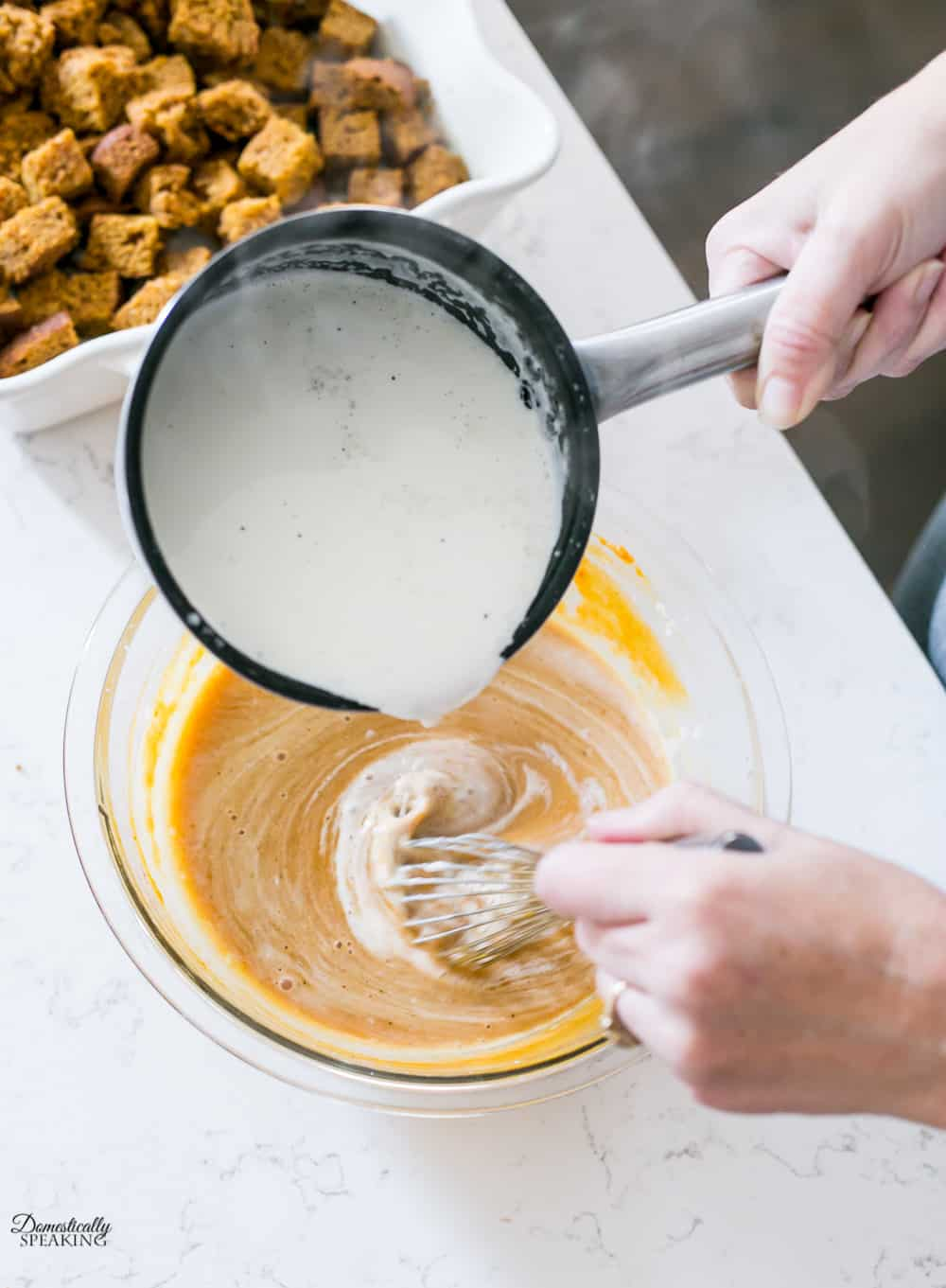 Tempering the egg mixture and cream mixture for pumpkin custard.