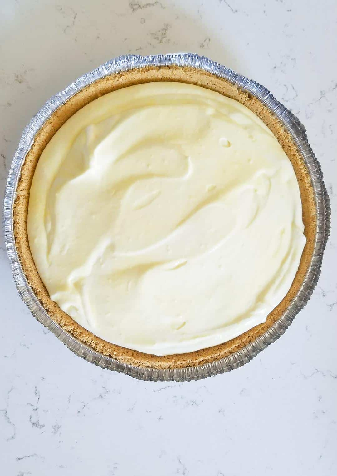 Adding the lemon cream pie filling to the graham cracker pie crust.