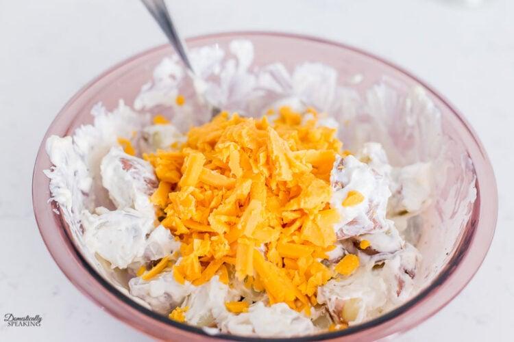 Adding cheese to loaded potato salad